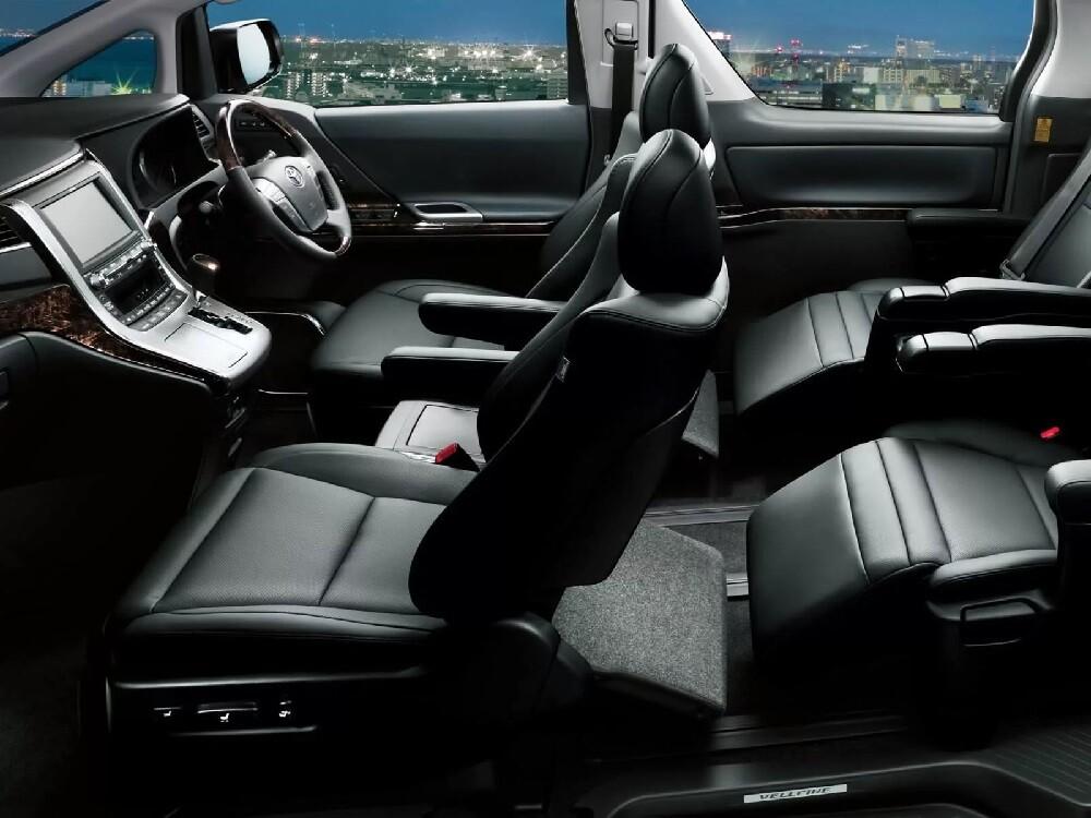 Toyota Alphard III поколения – это обновленный японский минивэн класса «М», получивший премиальный рестайлинг в 2018 году. За счет специфичности машины и внушительного ценника увидеть минивэн в России удается редко, поэтому стоит рассмотреть подробное описание Тойота Альфард 3 поколения, который стал после рестайлинга одним из самых стильных в сегменте. Внешний вид Тойота Альфард 3 Тойотe Альфард рестайлинг практически со всех сторон, начиная с решетки радиатора и заканчивая клиренсом. Автомобиль стал еще ярче отражать высший класс, благодаря чему спрос со стороны состоятельных покупателей заметно вырос по сравнению с 2015-2017 годами. Кузов Третье поколение минивэна условно делится на два выпуска: классический и рестайлинговый. длился с середины 2015 года по начало 2018 года. Toyota Alphard III по сравнению с предыдущим поколением получил более спортивные и резкие линии кузова, расширенное лобовое и новый дизайн боковых стекол. Передняя часть автомобиля оказалось более выраженной и агрессивной благодаря увеличенной решетке радиатора с измененной структурой и новым двухсекторным фарам с оригинальными ходовыми огнями. Рестайлинг 2018 года изменил существенно доработал образ минивэна. Решетка радиатора по сравнению с предыдущей версией продлилась практически до основания переднего бампера и получила стильные хромированные обрамления с ярко выраженным вертикальным узором. Задняя часть почти не претерпела изменений: лишь немного обновилась структура задних огней. Параметры Размеры кузова Тойота Альфард, как и подобает премиальному минивэну, впечатляют своим размахом. Длина автомобиля составила 4,945 м, ширина — 1,8 м, высота — 1,945 м, благодаря чему инженеры смогли предоставить достаточно пространства 7 пассажирам. Способствуют комфортным поездкам идеально подобранная колесная база (3 м), а также ширина передней и задней колея, размеры которых составляют 1,625 и 1,6 м соответственно. Тойота Альфард купить бу На фоне отличных внешних характеристик несколько огорчает кли